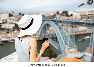 Young woman tourist sitting with glass of Porto wine on the terrace with great cityscape view on Porto city in Portugal