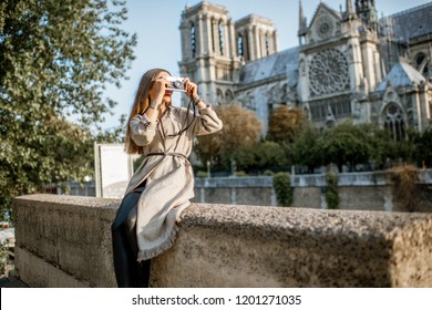 Young woman tourist sitting near the famous Notre Dame cathedral during the morning light traveling in Paris, France