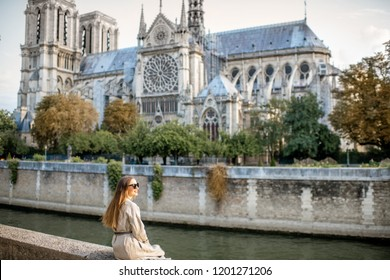 Young woman tourist sitting near the famous Notre Dame cathedral during the morning light traveling in Paris, France. Wide view with copy space