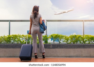 Young woman tourist is standing in airport and looking at aircraft flight through window. She is holding tickets and suitcase.