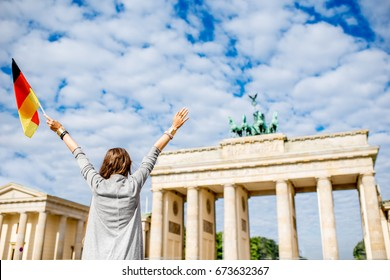 Young woman tourist standing back with raised hands and german flag in front of the famous Brandenburg gates in Berlin