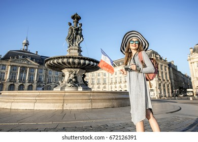 Young woman tourist standing with french flag on the famous de la Bourse square in Bordeaux city