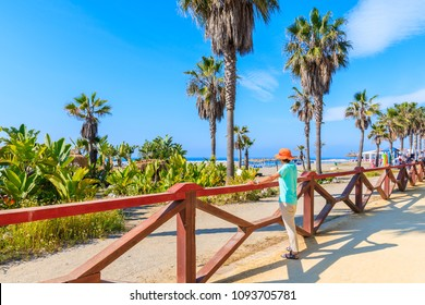 Young woman tourist standing on coastal promenade and looking at beautiful beach with palm trees near Marbella, Andalusia, Spain