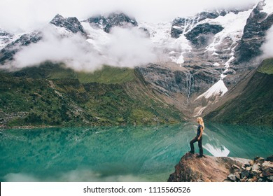 Young woman tourist standing on rock of hill admiring natural environment of high mountains covered white clouds during trip.Female traveller in active wear exploring beauty of Salkantay