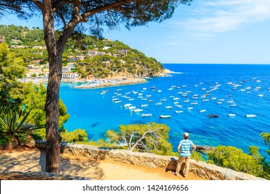 Young woman tourist standing on viewpoint over beautiful bay with boats on sea near Llafranc village, Costa Brava, Spain