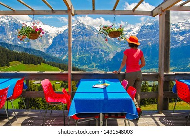 Young woman tourist standing on restaurant terrace and looking at Swiss Alps, Grindewald, Switzerland