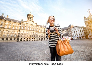 Young woman tourist standing with photo camera on the Dam central square during the morning in the old town of Amsterdam city