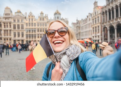 Young woman tourist stands with the flag of Belgium on the background of the Grand-Place or the Grand Market Square in Brussels