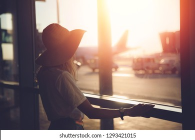 Young woman tourist in straw hat writes messages via smartphone at airport near terminal. Travel concept.
