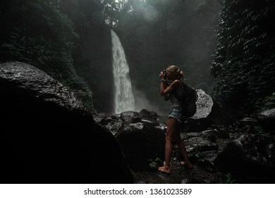 Young woman tourist taking photo of the Nung Nung waterfall, magic island of Bali, Indonesia.