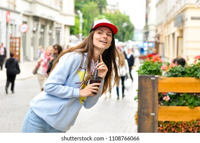 young woman tourist walking around the city and drinking a cold cocktail in hip hop style clothes
