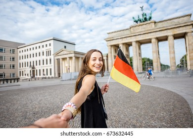 Young woman tourist walking with german flag to the famous Brandenburg gates in Berlin. Follow me concept