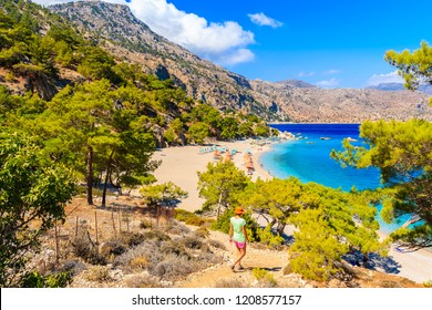 Young woman tourist walking on cliff path to beautiful Apella beach on Karpathos island, Greece