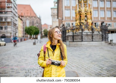 Young woman tourist in yellow raincoat standing on the main square of Nurnberg old town in Germany