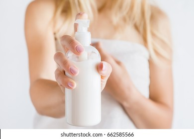 Young woman in towel after shower using body cream. Skin care.