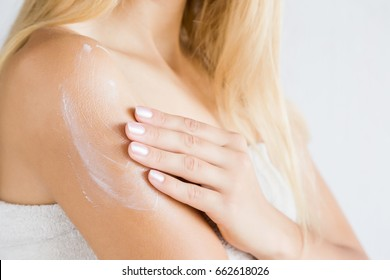 Young woman in towel after shower applying a body cream. Skin care.