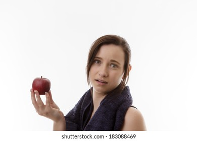 young woman with a towel around her neck holding a single apple