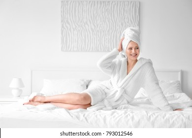 Young woman in towel and bathrobe sitting on bed at home
