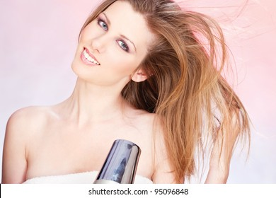 Young woman with towel holding blow dryer