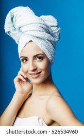 Young woman in towel on head after shower, blue background, smiling