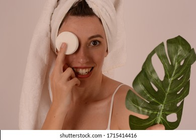 young woman with a towel on her head with a cotton pad near her eye fresh skin
