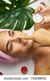 young woman with a towel on her head apply cream on her face, candles, body, skin, spa care