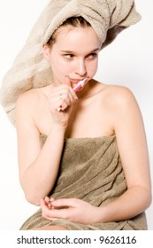 Young woman in towel on a white background cleaning her teeth