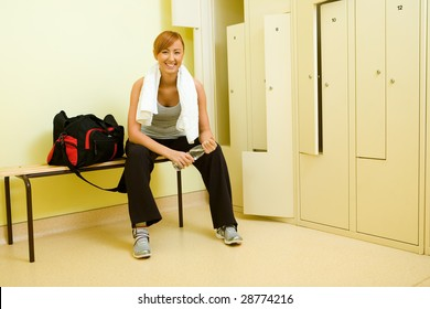 Young woman with towel sitting on bench in locker room. She's holding bottle of water.