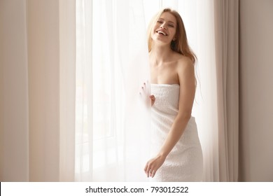 Young woman in towel standing near window at home
