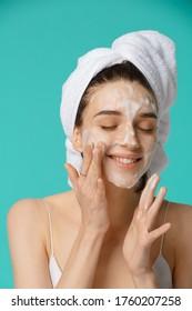 Junge Frau mit einem Handtuch umhüllt um den Kopf, indem sie Gesichtsputz aufträgt und Spaß hat. Alltägliche Routine - Gesichtspflege, Hautpflege, Schälen, Feuchtigkeitsspenden und Schönheitsbehandlungen