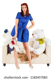 Young woman with toy bears sitting on a sofa
