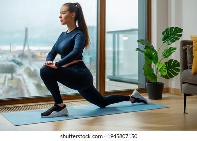 Junge Frau in Tracht trainiert im Yoga-Krieger auf Matte mit grüner Pflanze und Panoramafenster mit Blick auf die Stadt in Lodge