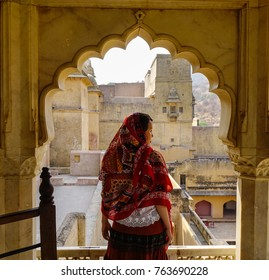 A young woman with traditional dress standing at an ancient palace in Jaipur, India.