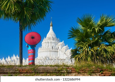 Young woman in traditional dress with an umbrella is looking at the Hsinbyume-Paya pagoda near the old town of Mandalay, Myanmar.