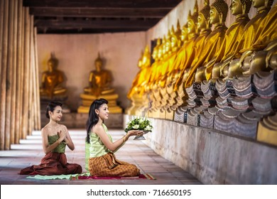 A young woman in traditional Thai dress to worship the Buddha and the servant girl next to her.