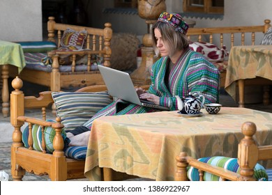 Young woman in traditional uzbek coat (chapan) scull cap with laptop by table with teapot and cup (piala). Uzbekistan, Central Asia.