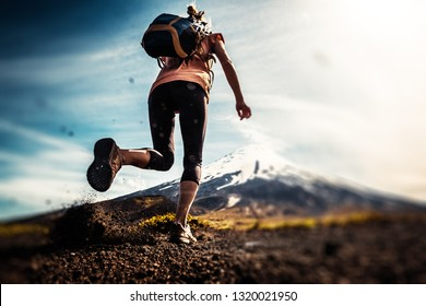Young woman, trail running athlete runs on the trail with loose ground and volcano on the background. Tilt shift effect applied