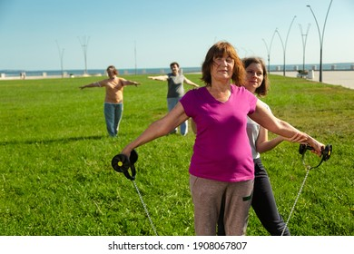 Young woman trainer helps senior woman doing stretching exercises. Healthy lifestyle after retirement. Fitness training in park for elderly people.