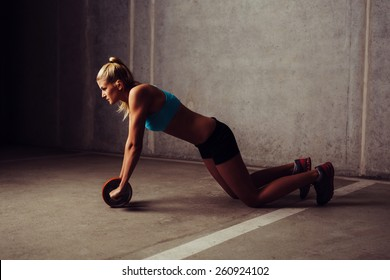 Young woman training with ab wheel