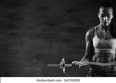 Young woman training with barbell. Black and white photo