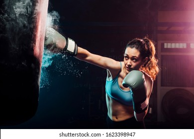 young woman training boxing in the punching bag - sport, self defense, boxing and training concepts - swing boxing
