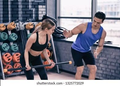Young woman training with coach in modern gym