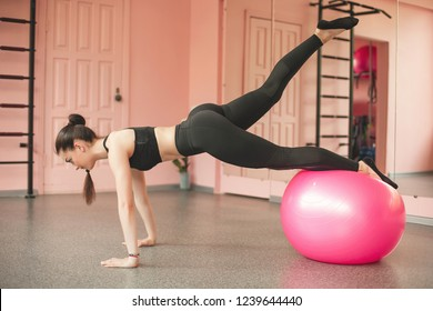 Young woman training in the gym with fitball. Personal trainer indoors workout. Exercises with fit ball.