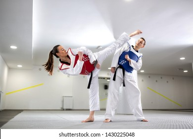 Young woman training martial art of taekwondo with her coach, sportsmanship concept
