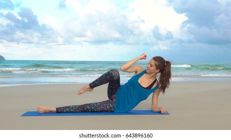 Young woman training on the beach in front of sea. Morning gymnastic. Side plank exercise. Healthy active lifestyle concept