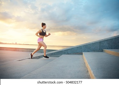 Young woman training on a morning run mounting a set of concrete steps outdoors against a glowing sunrise with cloud in a health and fitness concept