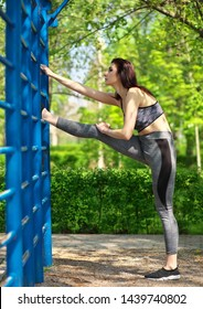 Young woman is training on the outdoor playground and pulls up on the horizontal bar. Gym open air fitness working out outdoor concept.