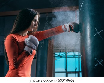 Young woman training punch boxing gloves for punching bag. Girl making Strong kick. Cross Fit.