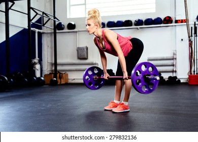 Young woman training Straight Leg Deadlift exercise at gym