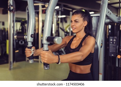 Young woman training upper body using fly machine